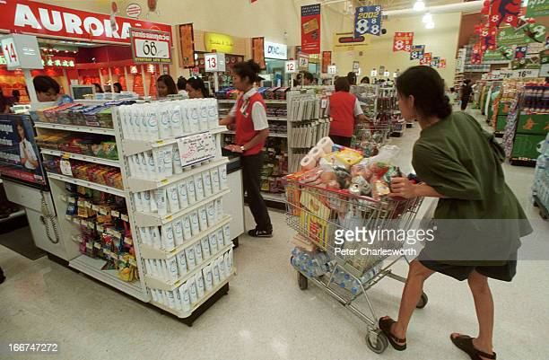 A customer pushes her fullyladen shopping cart towards the checkout counters of a Tesco Lotus shopping center in Bangkok The government of Thailand...