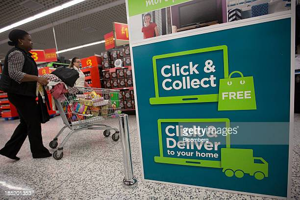 A customer pushes her shopping cart past a 'click and collect' point inside an Asda supermarket the UK retail arm of WalMart Stores Inc in Watford UK...