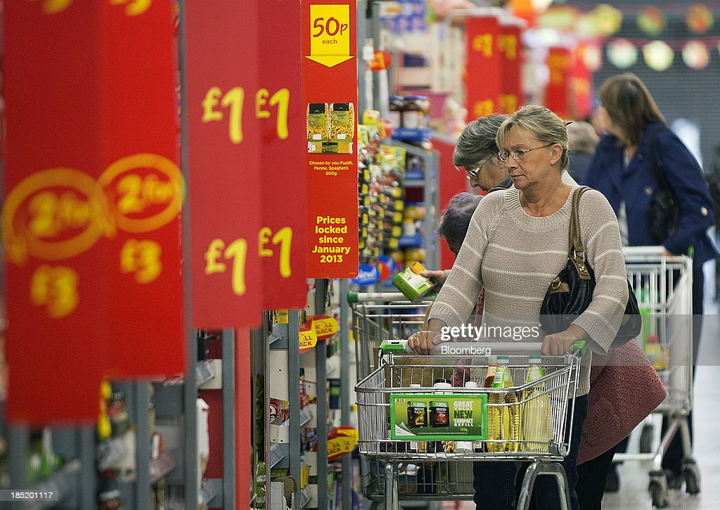 A customer pushes her shopping cart past a row of banners advertising reduced-priced goods inside an Asda supermarket, the U.K. retail arm of Wal-Mart Stores Inc., in Watford, U.K., on Thursday, Oct. 17, 2013. U.K. retail sales rose more than economists forecast in September as an increase in furniture demand led a rebound from a slump the previous month. Photographer: Simon Dawson/Bloomberg via Getty Images