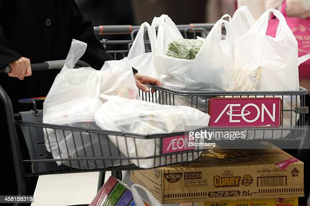 A customer pushes shopping carts bearing the Aeon Co logo at the Aeon Style Store in the Aeon Mall Makuhari Shintoshin shopping mall operated by Aeon...