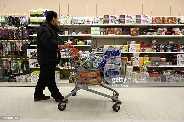 A customer pushing a shopping cart of products including cases of Oriental Brewery Co Cass beer walks past shelves of household items at an EMart Co...