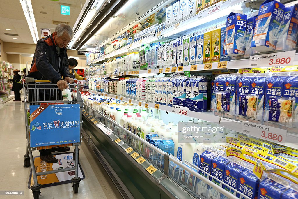 A customer puts a bottle of milk into a shopping cart at an E-Mart Co. store, a subsidiary of Shinsegae Co., in Incheon, South Korea, on Saturday, Dec. 21, 2013. Consumer prices climbed 0.9 percent in November from a year earlier after a 0.7 percent increase in October that was the smallest gain since July 1999. Photographer: SeongJoon Cho/Bloomberg via Getty Images