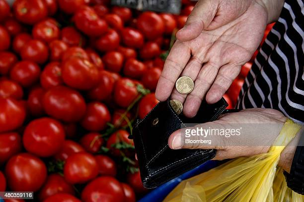 A customer puts euro coins into a wallet after purchasing produce at an open air street market in Athens Greece on Saturday July 11 2015 Both Prime...