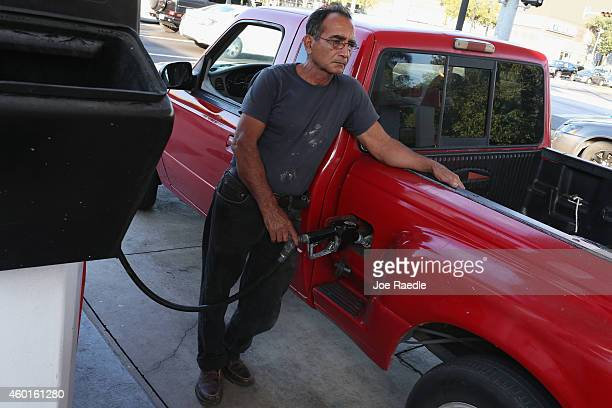 A customer puts gas into a vehicle at the Ugas station on December 8 2014 in Miami Florida According to the AAA Monthly Gas Price Report todays...
