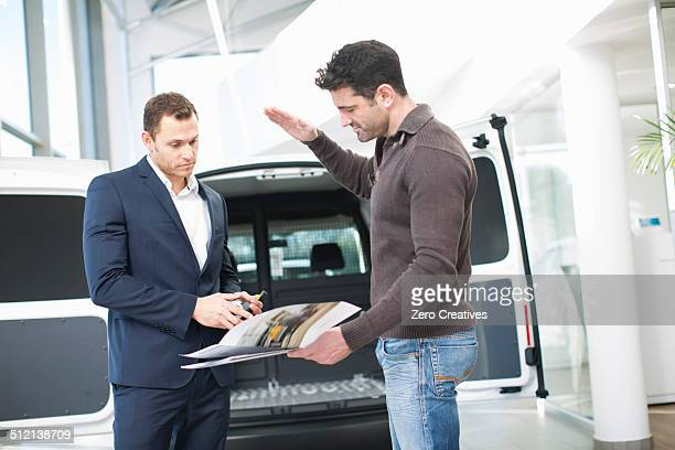 Customer questioning salesman in car dealership