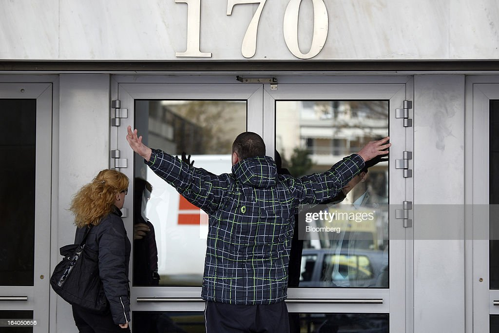 A customer raises his arms as he argues with staff for not allowing him inside a Bank of Cyprus Plc branch as he tries to withdraw cash without a bank card in Athens, Greece, on Tuesday, March 19, 2013. Cyprus's passage of an unprecedented levy on bank deposits was in doubt as euro-area finance ministers responded to criticism of the measure by loosening their stance on how the money is raised. Photographer: Kostas Tsironis/Bloomberg via Getty Images