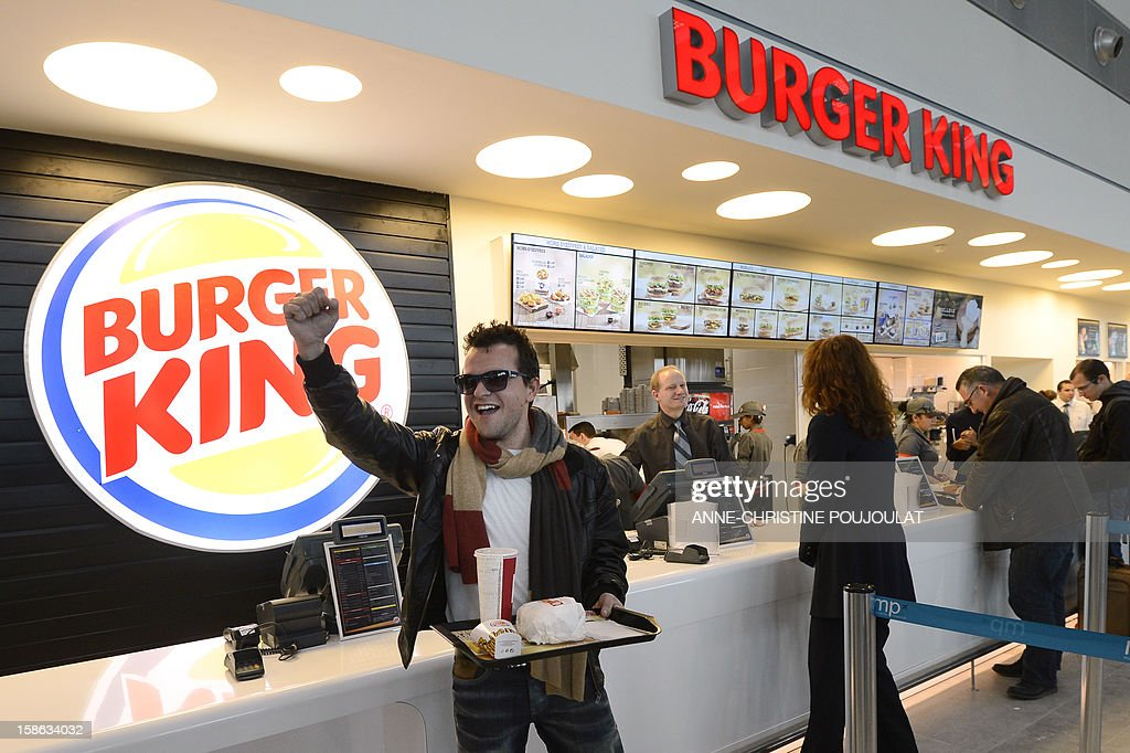 A customer reacts after being served at the Burger King fast food restaurant in Marseille's airport, in Marignane, southern France, on December 22, 2012. Marignane's Burger King is the first shop of the brand to open in France after 15 years of absence and marks the return of the famous Whopper burger in the country.