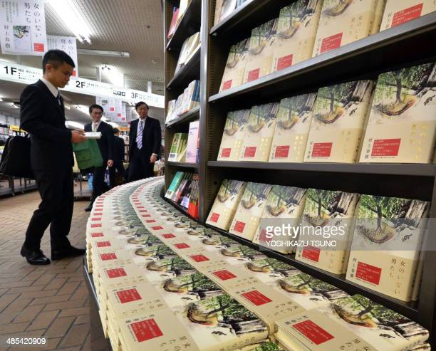 A customer reads a book by Japanese author Haruki Murakami as Murakami's new novels of the book 'Onna no Inai Otokotachi' which can be translated as...