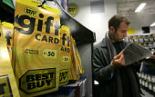 A customer reads a magazine near a display of Best Buy gift cards at a Best Buy store December 29 2005 in San Francisco California Retailers...