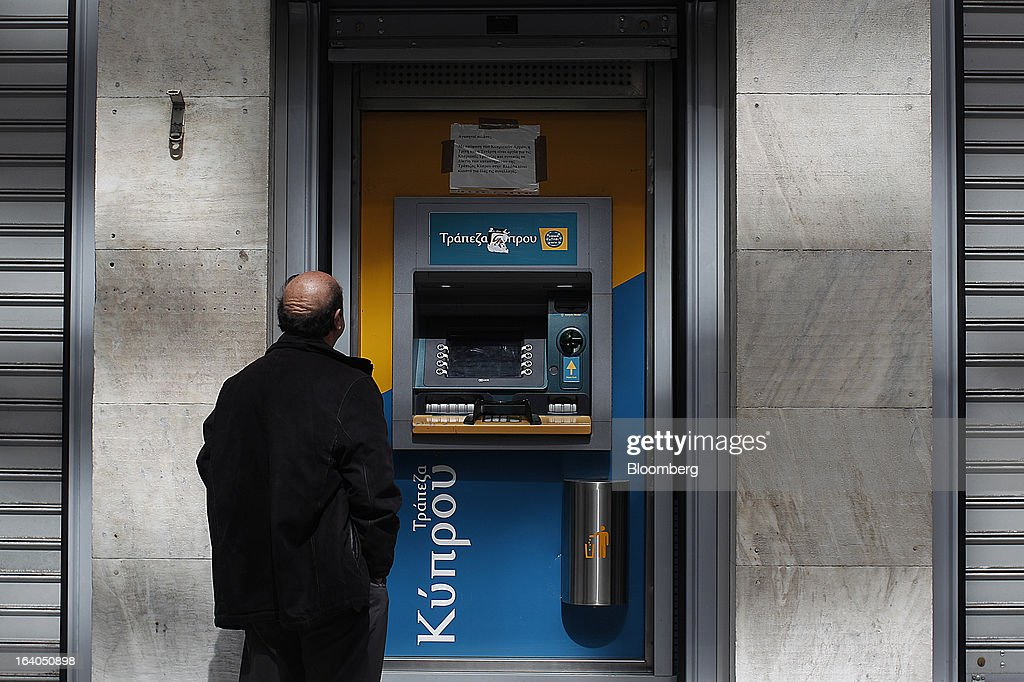 A customer reads a notice which says only automated teller machines (ATM) are open outside a closed Bank of Cyprus Plc branch in Athens, Greece, on Tuesday, March 19, 2013. Cyprus's passage of an unprecedented levy on bank deposits was in doubt as euro-area finance ministers responded to criticism of the measure by loosening their stance on how the money is raised. Photographer: Kostas Tsironis/Bloomberg via Getty Images