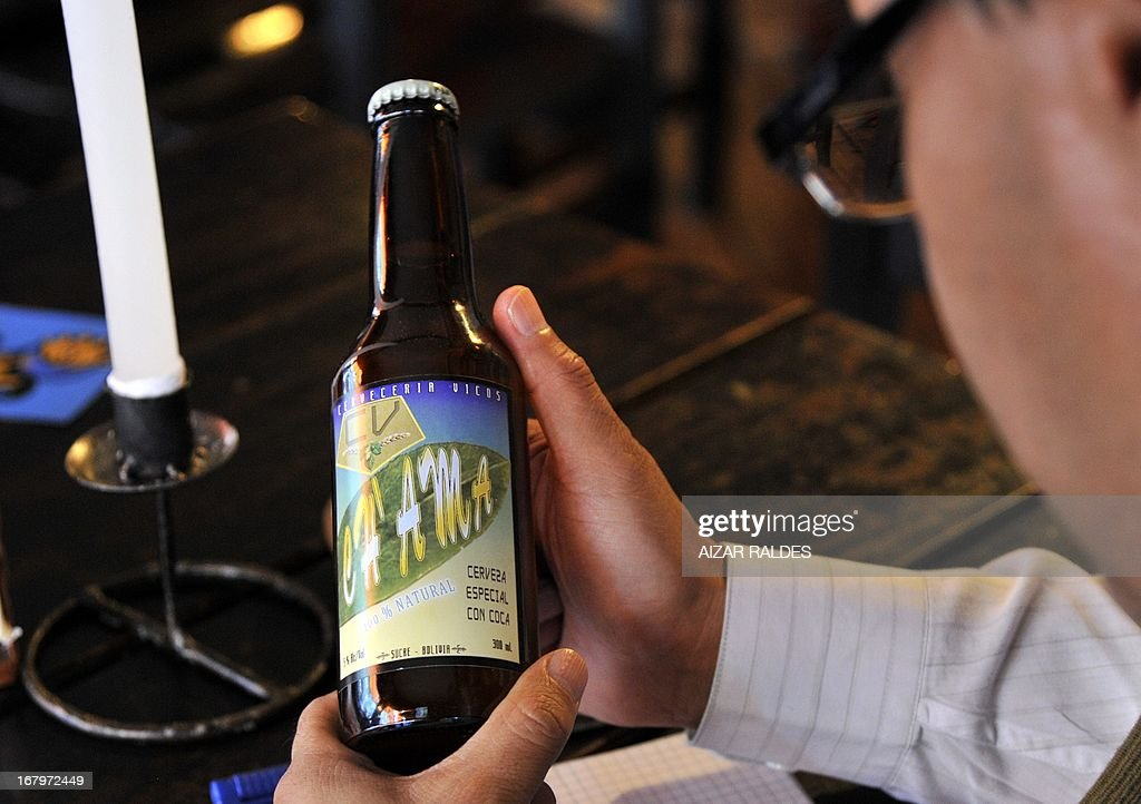 A customer reads the label of a bottle of Ch'ama, a coca leaves and barley based beer in a bar in La Paz, on May 2, 2013. The beer, made with organic barley and coca, have the same alcohol content that a normal one, and is mainly consumed by European tourists. AFP PHOTO / Aizar Raldes