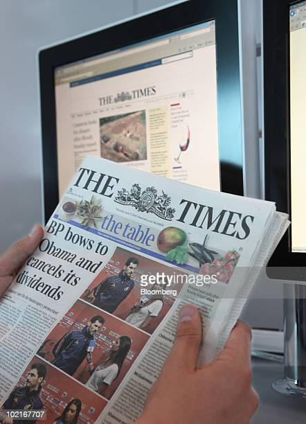 A customer reads the The Times newspaper in front of the newspaper's website in London UK on Thursday June 17 2010 The newspaper this week began...