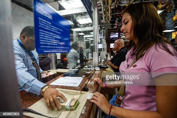 A customer receives money at a currency exchange office in Caracas on February 19 2015 The Venezuelan bolivar opened Thursday at 172 to the dollar on...
