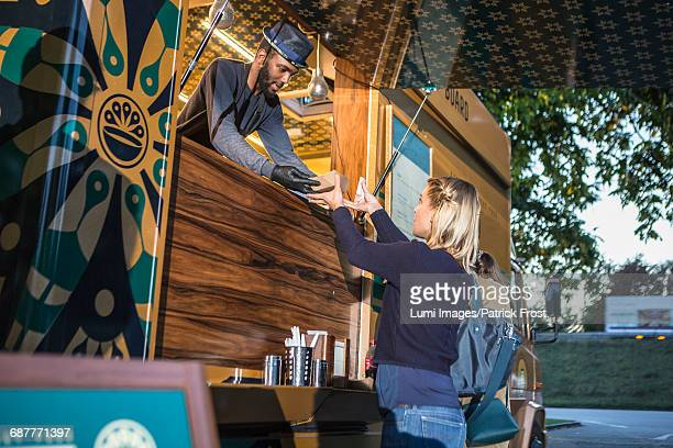 Customer receiving food from vendor at food truck