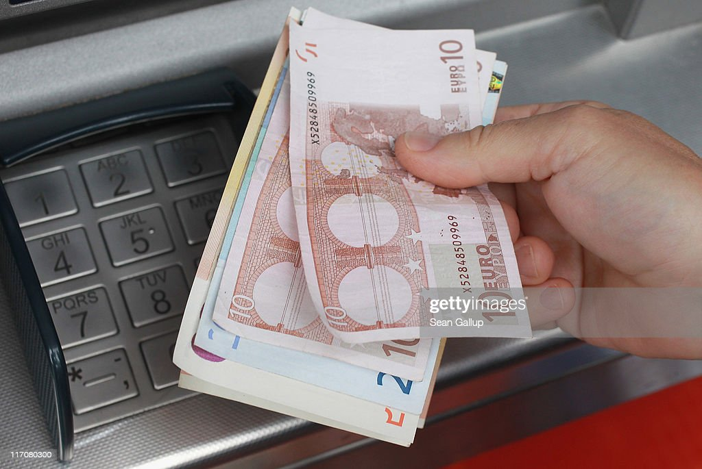 A customer removes Euro currency bills from a cash machine on June 21, 2011 in Berlin, Germany. Eurozone finance ministers are currently seeking to find a solution to Greece's pressing debt problems, including the prospect of the country's inability to meet its financial obligations unless it gets a fresh, multi-billion Euro loan by July 1. Greece's increasing tilt towards bankruptcy is rattling worldwide financial markets, and leading economists warn that bankruptcy would endanger the stability of the Euro and have dire global consequences.