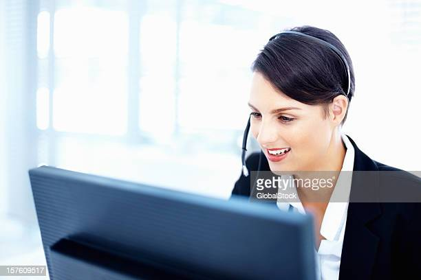 Customer representative wearing headset and working on computer