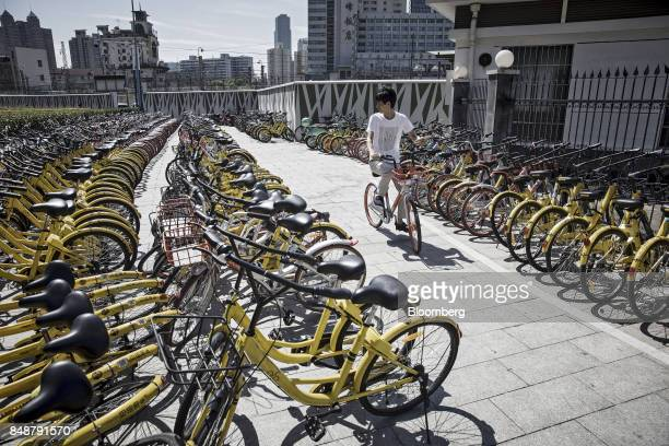 A customer rides a BeijingMobikeTechnology Co bicycle from a designated parking space outside a subway station in Shanghai China on Thursday Sept...