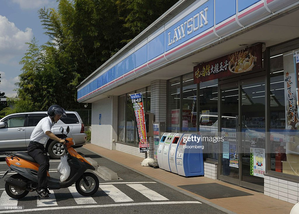 A customer rides his motorcycle in front of a Lawson Inc. convenience store in Yokohama City, Kanagawa Prefecture, Japan, on Tuesday, Sept. 11, 2012. Sales at Japan's convenience stores declined 3.3 percent in July from a year ago on a same-store basis, according to the Japan Franchise Association. Photographer: Akio Kon/Bloomberg via Getty Images