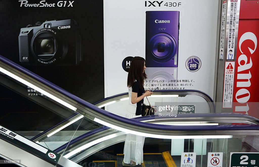 A customer rides on an escalator in front of advertisements for Canon Inc. digital cameras at an electronics store in Tokyo, Japan, on Tuesday, July 23, 2013. Canon Inc., the world's largest camera maker, is scheduled to release earnings on July 24. Photographer: Tomohiro Ohsumi/Bloomberg via Getty Images