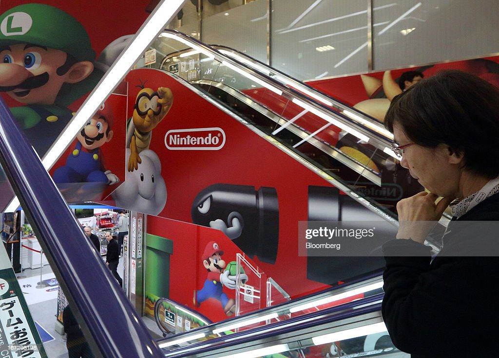 A customer rides on an escalator past an advertisement for Nintendo Co. at an electronics store in Tokyo, Japan, on Tuesday, April 23, 2013. Nintendo, the world's largest maker of video-game machines, will announce earnings on April 24. Photographer: Tomohiro Ohsumi/Bloomberg via Getty Images