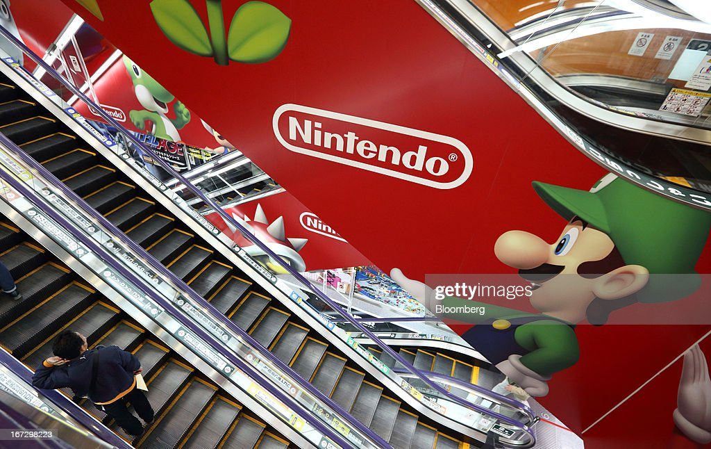 A customer rides on an escalator past an advertisement of Nintendo Co. at an electronics store in Tokyo, Japan, on Tuesday, April 23, 2013. Nintendo, the world's largest maker of video-game machines, will announce earnings on April 24. Photographer: Tomohiro Ohsumi/Bloomberg via Getty Images