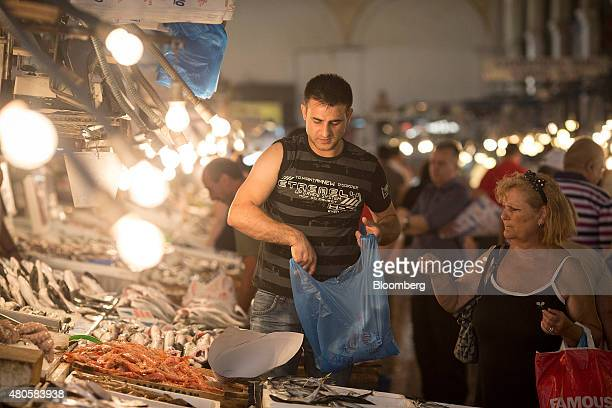 A customer right buys fresh fish from a vendor inside Varvakeios fish and meat market in Athens Greece on Monday July 13 2015 Greece has been in...