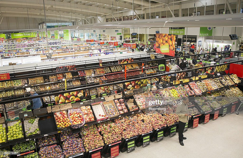 A customer, right, checks his personal mobile device as he stands near a display of apples in the fruit and vegetable display aisle inside an Asda supermarket in Wembley, London, U.K., on Friday, Nov. 29, 2013. Britons queued outside Asda supermarkets this morning and charged into stores when doors opened at 8 a.m. as the U.K. grocery chain took on the Black Friday mantle from U.S. owner Wal-Mart Stores Inc. Photographer: Simon Dawson/Bloomberg via Getty Images