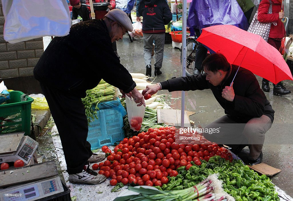 A customer, right, purchases tomatoes from a vendor at a market in Shanghai, China, on Thursday, Feb. 7, 2013. China's consumer prices rose 2 percent in January from a year earlier while the producer-price index dropped 1.6 percent, the National Bureau of Statistics said today in Beijing. Photographer: Tomohiro Ohsumi/Bloomberg via Getty Images