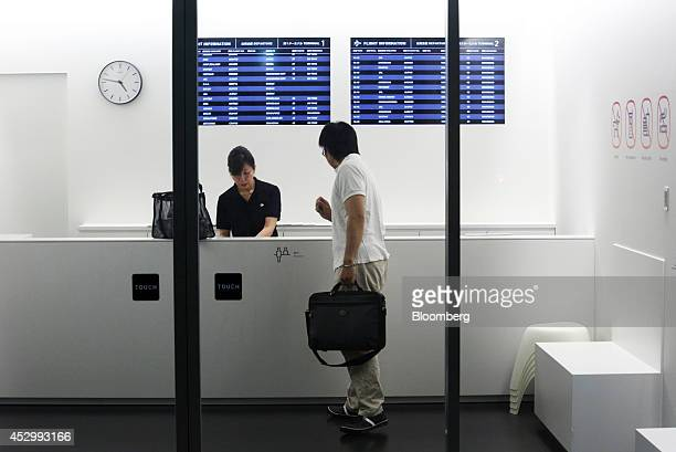 A customer right speaks to a receptionist at the reception of the Nine Hours Narita Airport capsule hotel operated by nine hours Inc at Narita...