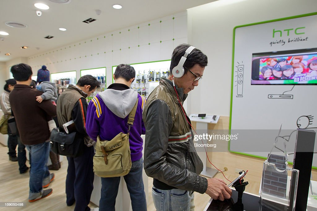 A customer, right, tries out an HTC Corp. One X+ smartphone at one of the company's stores in Taipei, Taiwan, on Sunday, Jan. 6, 2013. HTC is scheduled to release fourth-quarter earnings on Jan. 7. Photographer: Maurice Tsai/Bloomberg via Getty Images