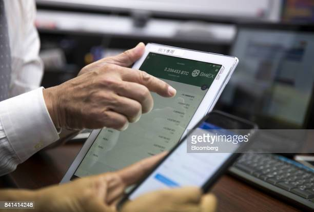 A customer right uses a smartphone as he sells bitcoin at the Coin Trader bitcoin retail store in Tokyo Japan on Wednesday Aug 30 2017 Stock of...