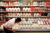 A customer scans the expiration date on gallons of milk sitting on a cooler shelf at a Safeway grocery store August 20 2007 in Washington DC The US...