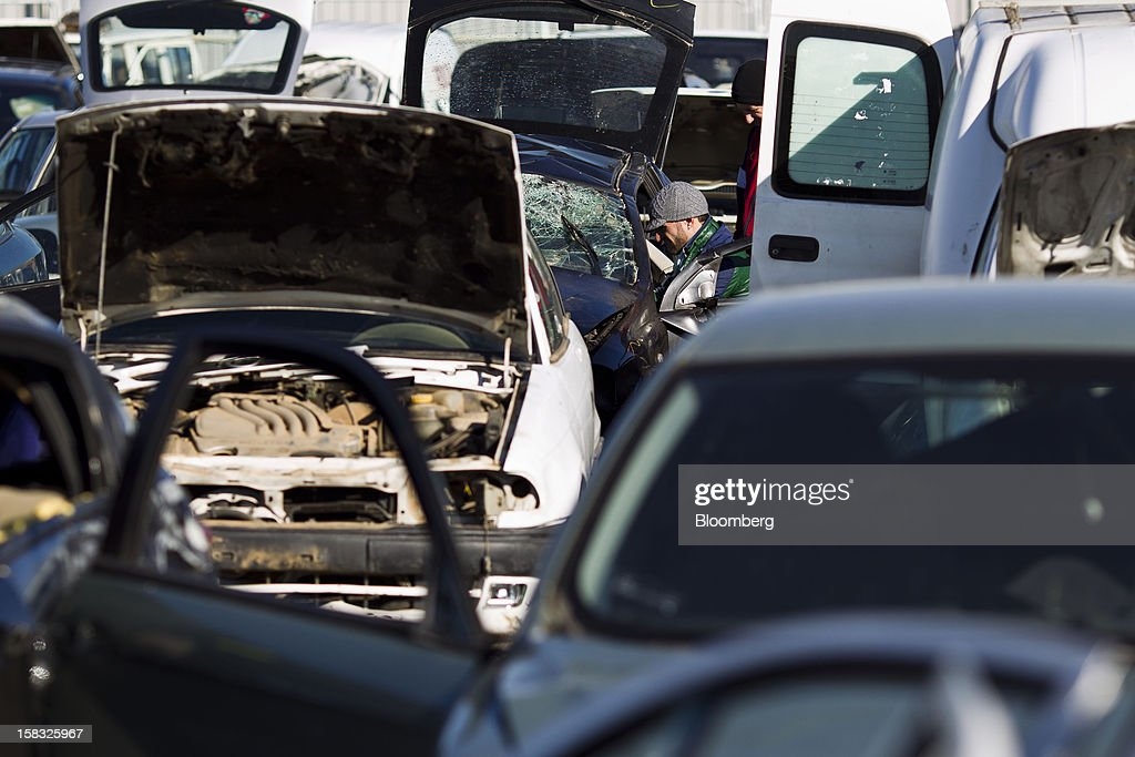 A customer searches for a spare part from a scrapped automobile in the yard of the Desguaces La Torre scrapyard in Madrid, Spain, on Thursday, Dec. 13, 2012. Spain has completed the debt sales it planned for this year and started raising funds for 2013, buying time for Prime Minister Mariano Rajoy as he decides whether to seek a European bailout. Photographer: Angel Navarrete/Bloomberg via Getty Images