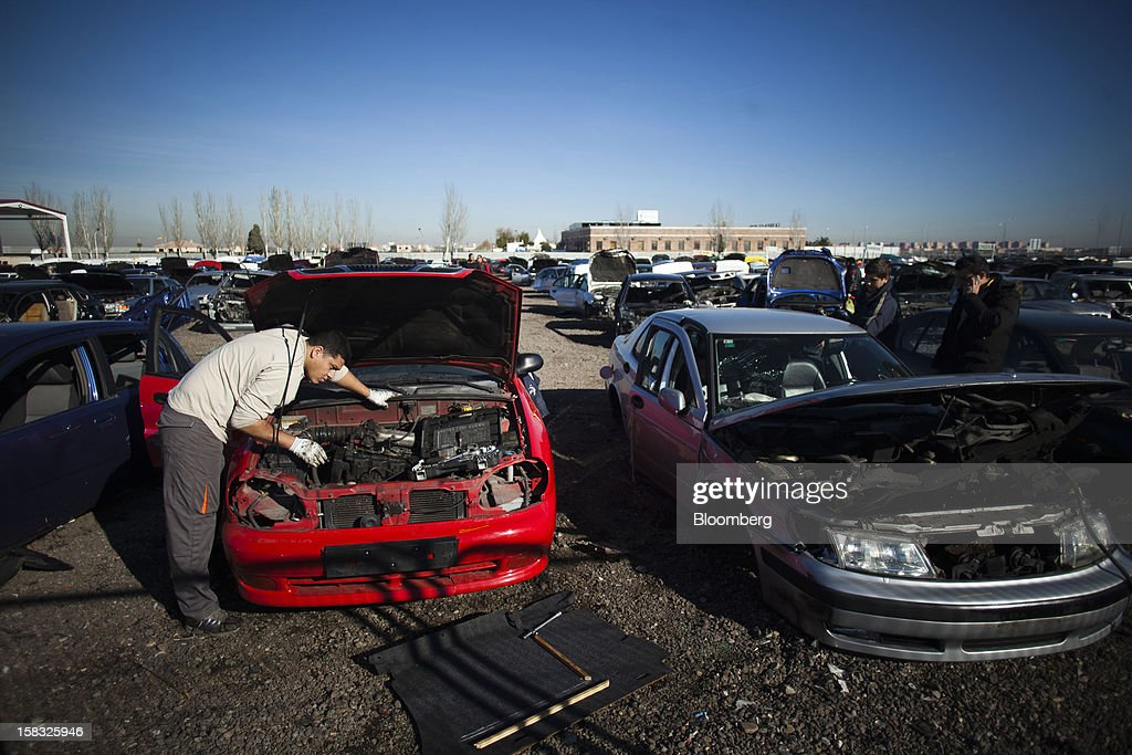 A customer searches for spare engine parts beneath the bonnet of a scrapped automobile in the yard of the Desguaces La Torre scrapyard in Madrid, Spain, on Thursday, Dec. 13, 2012. Spain has completed the debt sales it planned for this year and started raising funds for 2013, buying time for Prime Minister Mariano Rajoy as he decides whether to seek a European bailout. Photographer: Angel Navarrete/Bloomberg via Getty Images