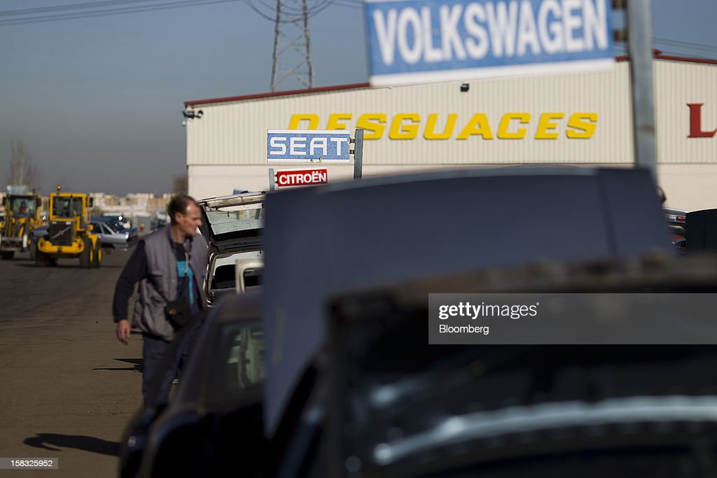 A customer searches for vehicle parts near signs for scrapped Seat, Volkswagen AG and PSA Peugeot Citroen automobiles in the yard of the Desguaces La Torre scrapyard in Madrid, Spain, on Thursday, Dec. 13, 2012. Spain has completed the debt sales it planned for this year and started raising funds for 2013, buying time for Prime Minister Mariano Rajoy as he decides whether to seek a European bailout. Photographer: Angel Navarrete/Bloomberg via Getty Images