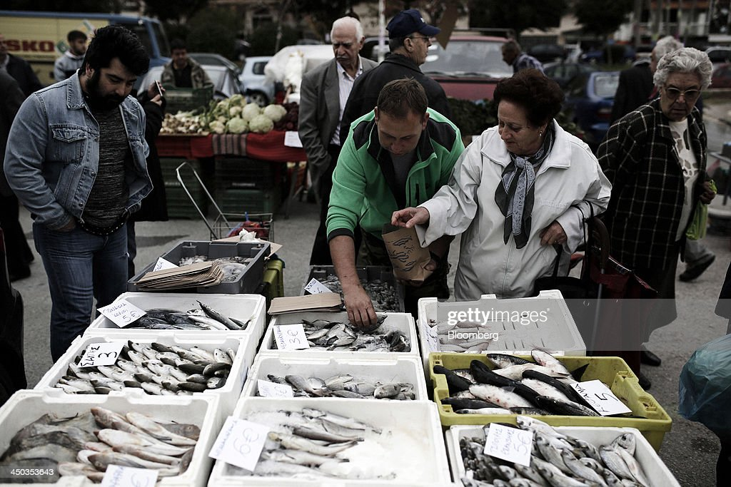A customer, second right, selects fresh fish from a stall at a farmers' market in Thessaloniki, Greece, on Saturday, Nov. 16, 2013. Greek Prime Minister Antonis Samaras, who survived a no-confidence vote on Nov. 11 with his parliamentary majority reduced to four, is trumpeting the first economic growth in seven years for 2014. Photographer: Konstantinos Tsakalidis/Bloomberg via Getty Images
