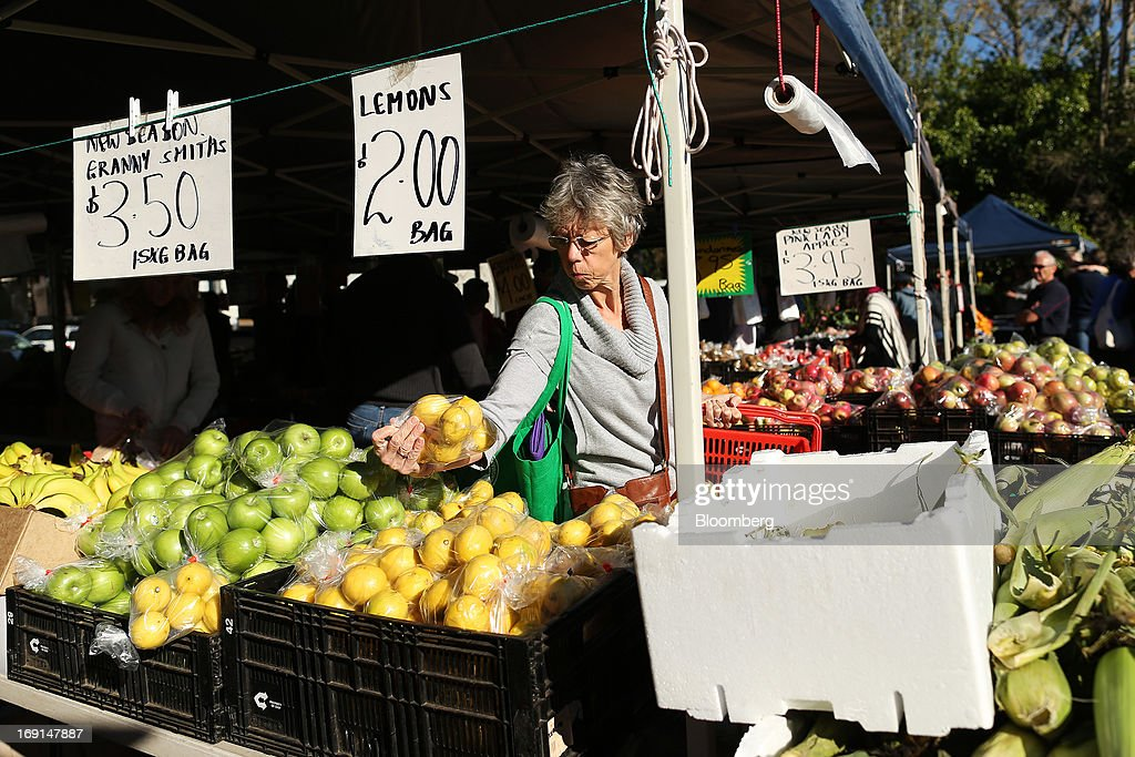 A customer selects a bag of lemons at a stall at the Frenchs Forest Organic Food Market in Sydney, Australia, on Sunday, May 19, 2013. The Reserve Bank of Australia cut its benchmark interest rate to a record low this month to boost businesses weakened by the currency's sustained strength, even as households reacted to earlier reductions. Photographer: Brendon Thorne/Bloomberg via Getty Images