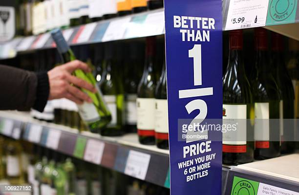 A customer selects a bottle of New Zealand white wine from a shelf at a supermarket in London UK on Wednesday Nov 16 2010 Majestic Wine Plc Chief...