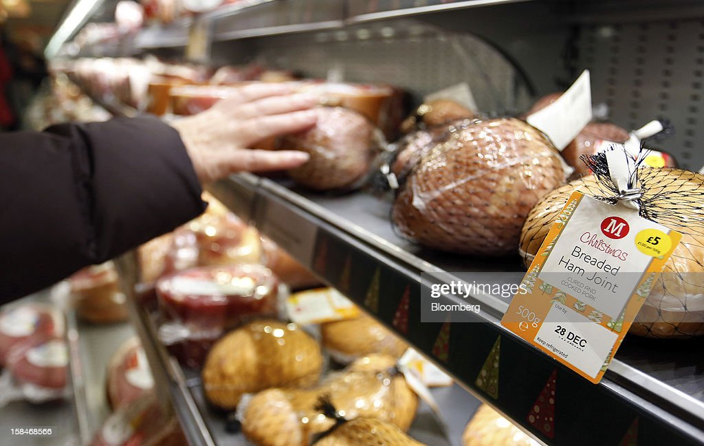 A customer selects a breaded ham joint from the chilled meat section inside a Morrisons supermarket, operated by William Morrisons Supermarkets Plc, in Chadderton, U.K., on Monday, Dec. 17, 2012. The British Christmas is the biggest epicurean occasion of the year, with households spending a total of 4 billion pounds on food in the final week before Dec. 25. Photographer: Paul Thomas/Bloomberg via Getty Images