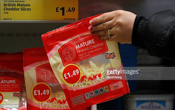 A customer selects a Cheese Emporium branded bag of British mature grated cheddar cheese at a supermarket operated by Aldi Group Germany's biggest...
