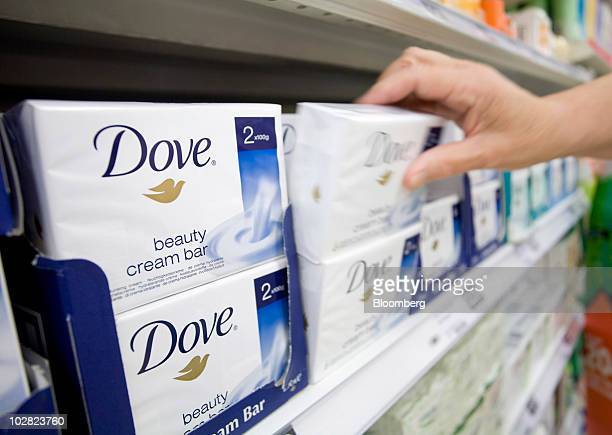 A customer selects a packet of Dove soap produced by Unilever Plc from the display at a supermarket in London UK on Friday July 9 2010 Unilever the...