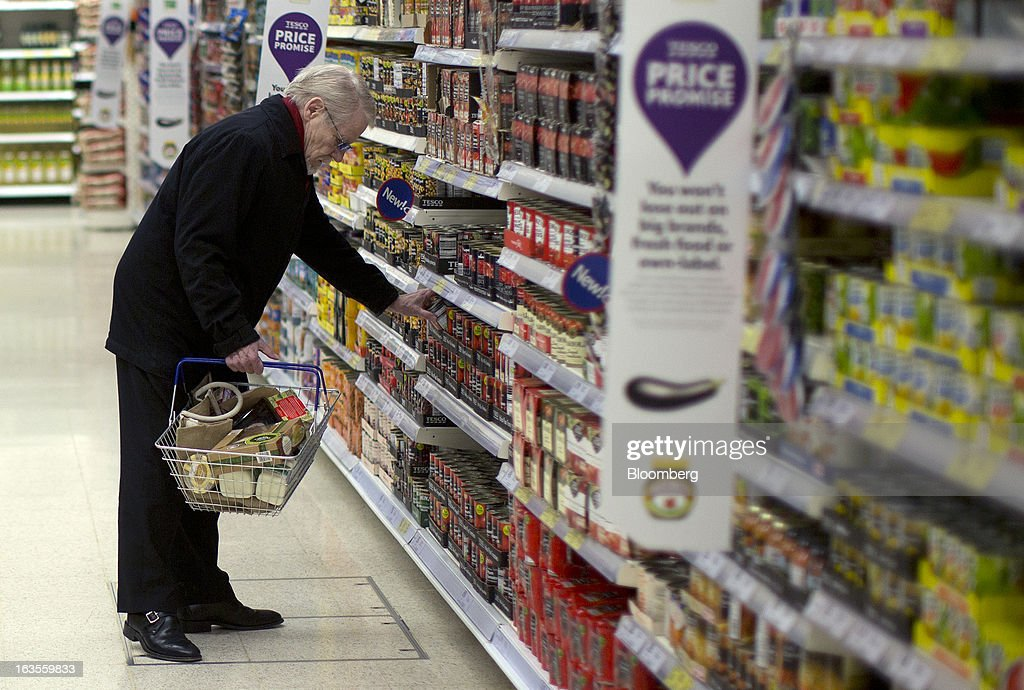 A customer selects a tin of tomatoes from a shelf inside a Tesco Plc supermarket in the borough of Kensington in London, U.K., on Tuesday, March 12, 2013. Tesco Plc, the U.K.'s largest grocer launched a 'Price Promise', its latest initiative offering to match the price of customers' purchases to that of it's rivals, including Wal-Mart Stores Inc.'s ASDA. Photographer: Simon Dawson/Bloomberg via Getty Images