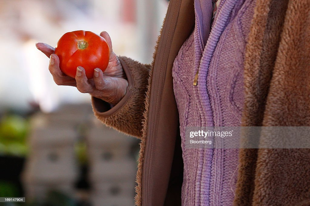 A customer selects a tomato at the Frenchs Forest Organic Food Market in Sydney, Australia, on Sunday, May 19, 2013. The Reserve Bank of Australia cut its benchmark interest rate to a record low this month to boost businesses weakened by the currency's sustained strength, even as households reacted to earlier reductions. Photographer: Brendon Thorne/Bloomberg via Getty Images