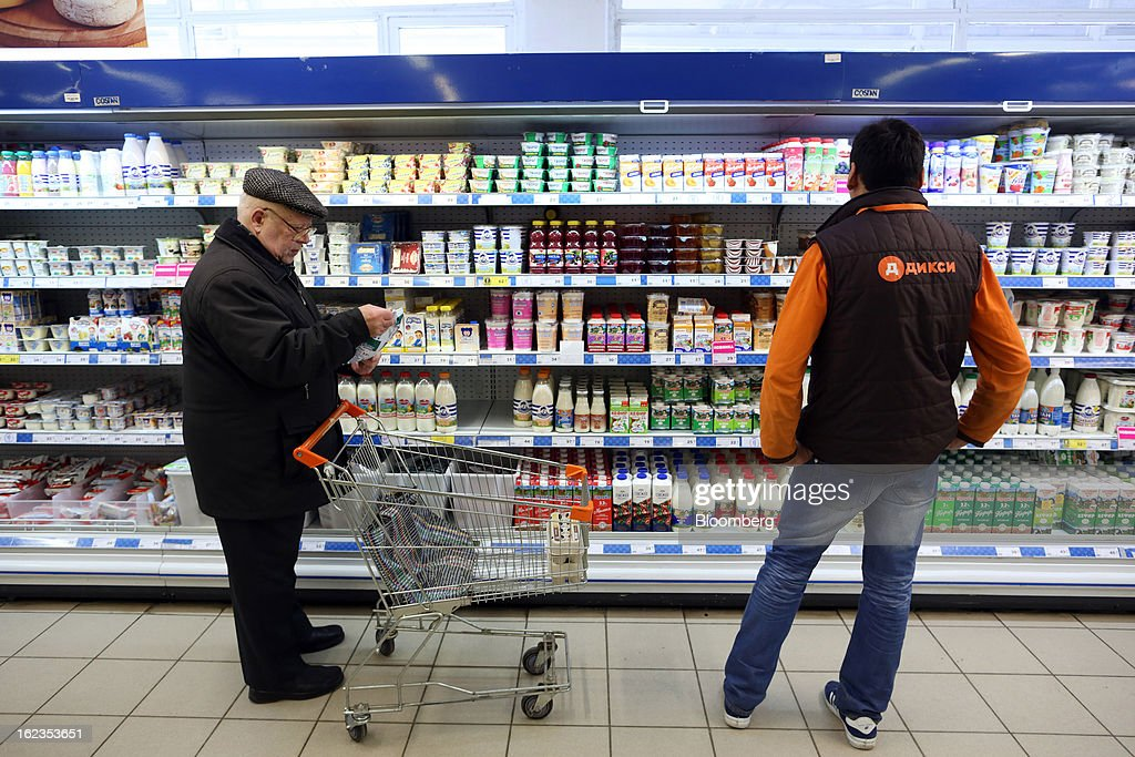 A customer selects an item for his shopping cart while an employee checks the chilled dairy section of a supermarket operated by OAO Dixy Group in Moscow, Russia, on Friday, Feb. 22, 2013. Russia's largest retailer by market value, OAO Magnit, is spending as much as $1.8 billion this year to compete against X5 Retail Group NV and OAO Dixy Group. Photographer: Andrey Rudakov/Bloomberg via Getty Images