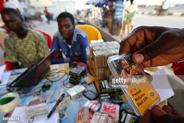 A customer selects an MTN Group Ltd prepaid mobile phone sim card at a roadside kiosk in Lagos Nigeria on Saturday Oct 31 2015 MTN Africa's largest...