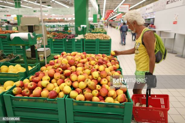 A customer selects apples in the fruit section of an Auchan Holding SA city supermarket operated by Groupe Auchan SA in Moscow Russia on Tuesday Aug...