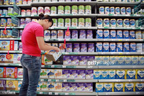 A customer selects baby milk in a supermarket in Haikou south China's Hainan province on August 7 2013 China has fined six mostly foreign baby...