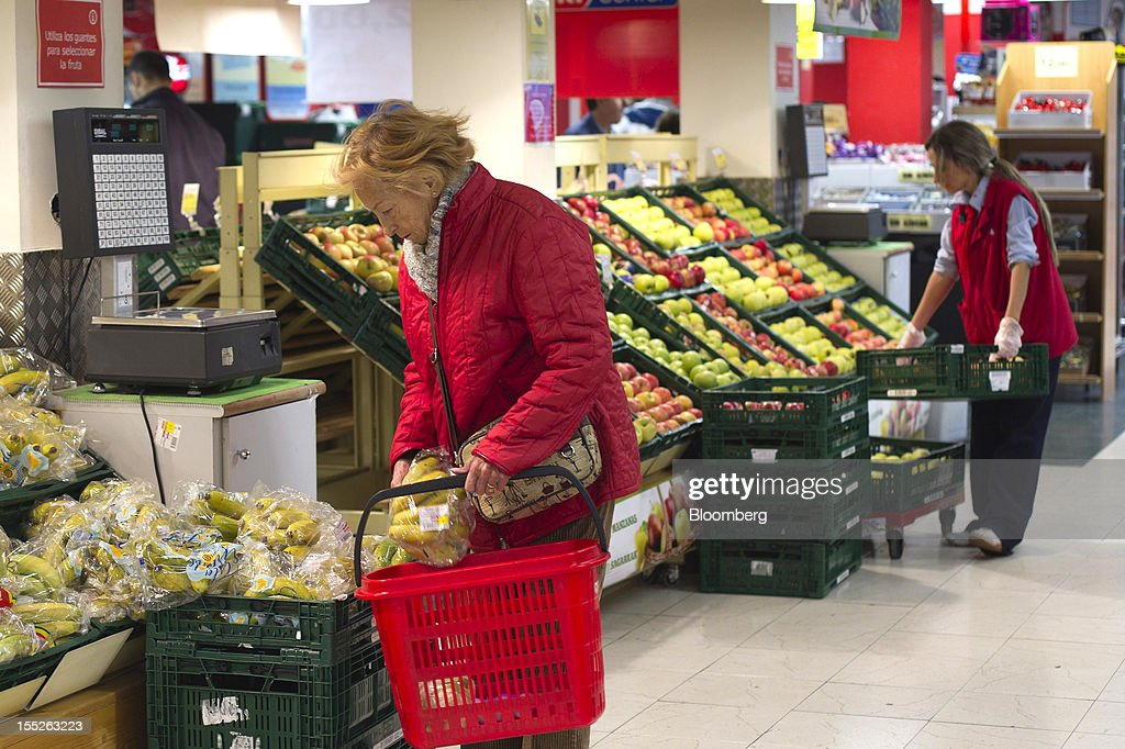 A customer selects bananas, left, for her shopping basket while an employee arranges a fruit display inside an Eroski Group supermarket in Madrid, Spain, on Friday, Nov. 2, 2012. Spain is unlikely to need a full bailout while any request from the euro area's fourth-largest economy for alternative support measures must be met with a swift response, Finnish Prime Minister Jyrki Katainen said. Photographer: Angel Navarrete/Bloomberg via Getty Images