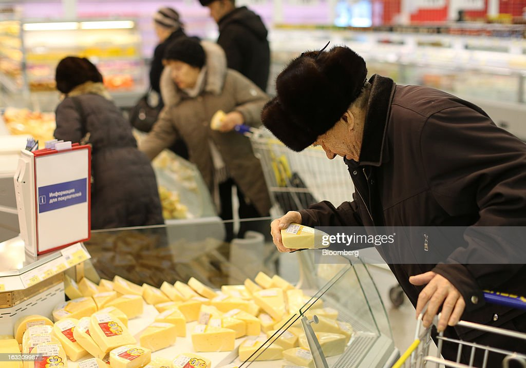 A customer selects cheese from a counter inside a Lenta LLC supermarket in Prokopyevsk, Kemerevo region, Russia, on Wednesday, March 6, 2013. Lenta LLC, a Russian hypermarket operator controlled by TPG Capital, is selling its first bond to expand after using company funds for a leveraged buyout by the U.S. firm. Photographer: Andrey Rudakov/Bloomberg via Getty Images