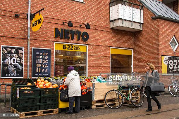 A customer selects fresh fruit for sale outside a Netto supermarket operated by Dansk Supermarked A/S in Copenhagen Denmark on Tuesday Jan 7 2014 AP...